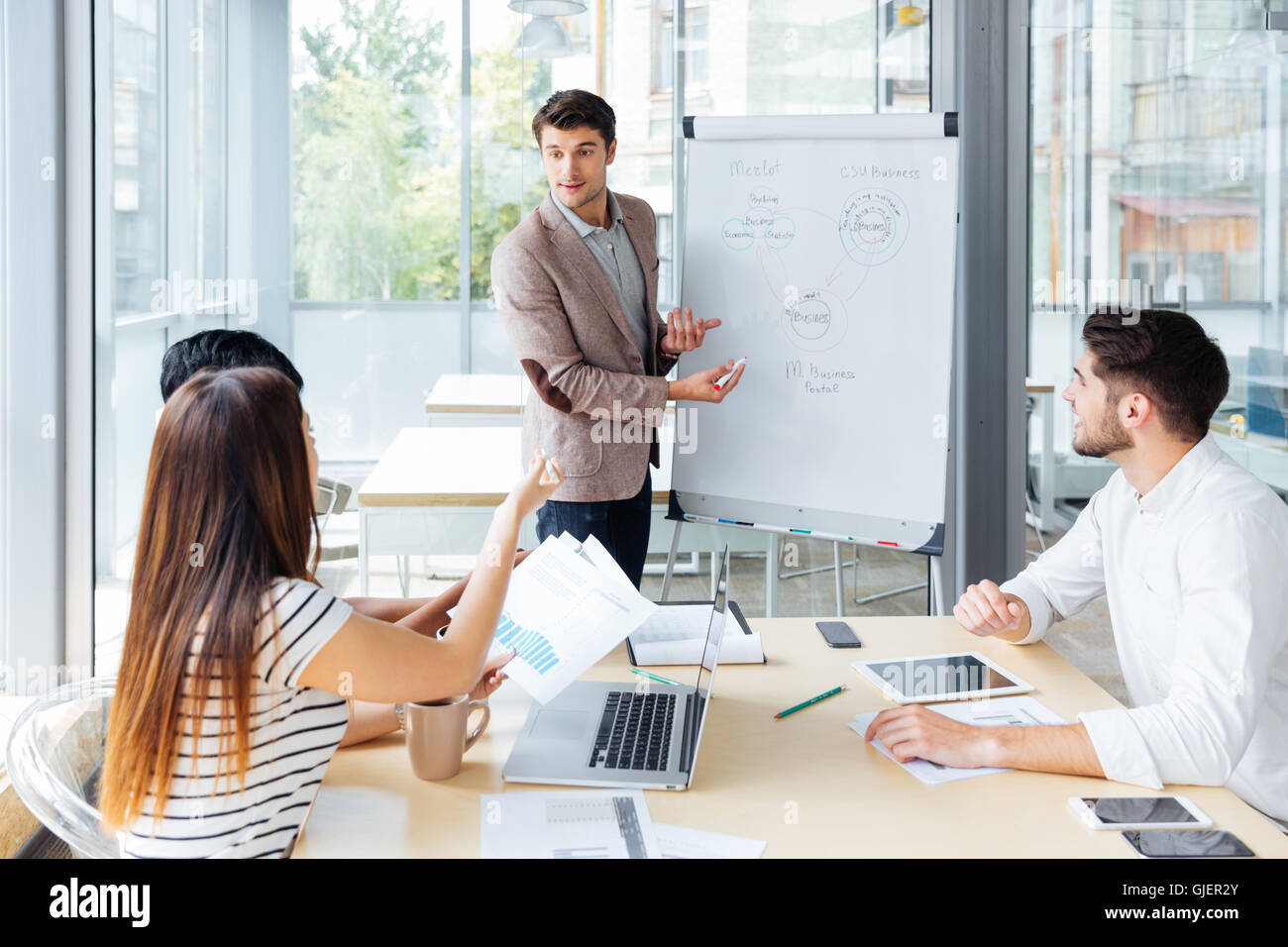 Confident handsome young businessman giving presentation using flipchart in office - Stock Image