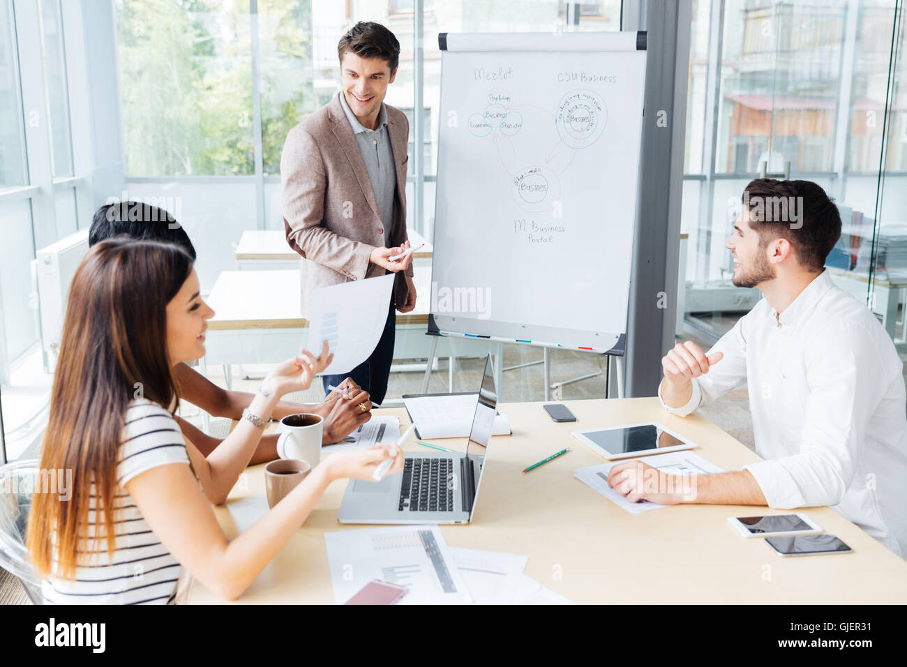 Happy attractive young businessman making presentation for business people in office - Stock Image