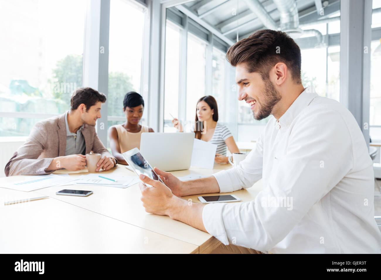 Happy handsome young businessman sitting and using tablet on business meeting - Stock Image