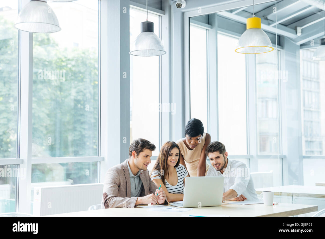 Multiethnic group of young business people creating presentation and using laptop together in office - Stock Image