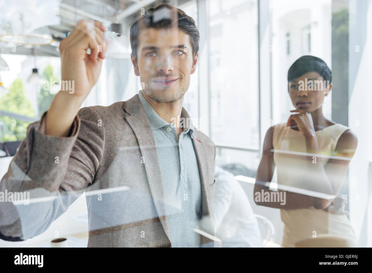 Concentrated young businessman working with african businesswoman and writing on transparent board in office Stock Photo