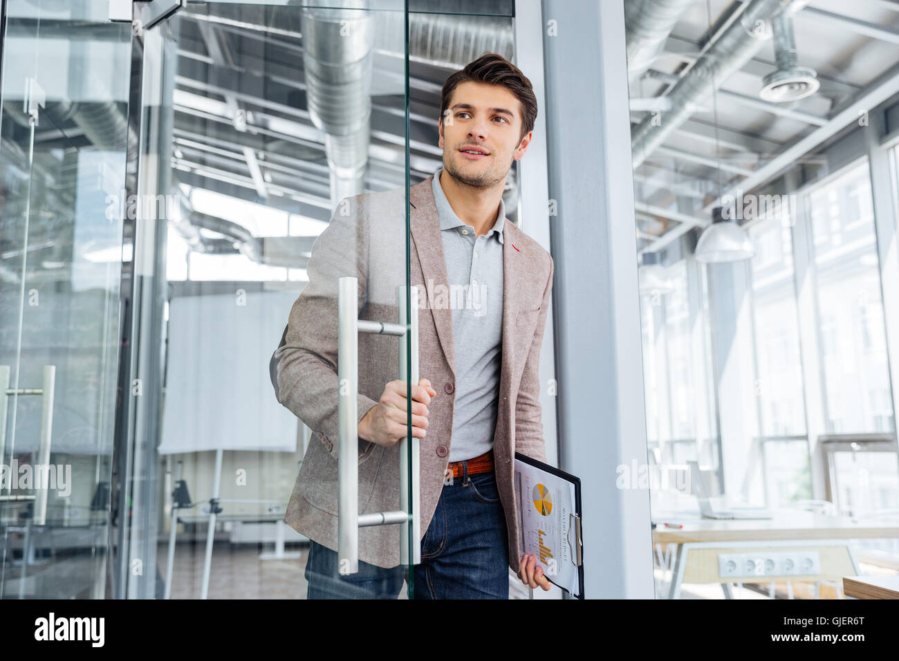 Handsome young businessman with clipboard entering the door in office - Stock Image
