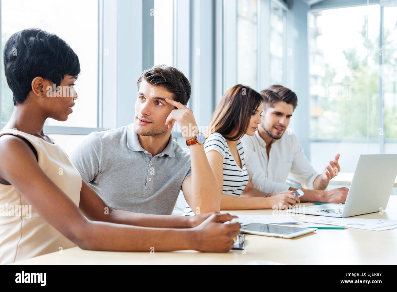 Group of young business people sitting and talking in office - Stock Image