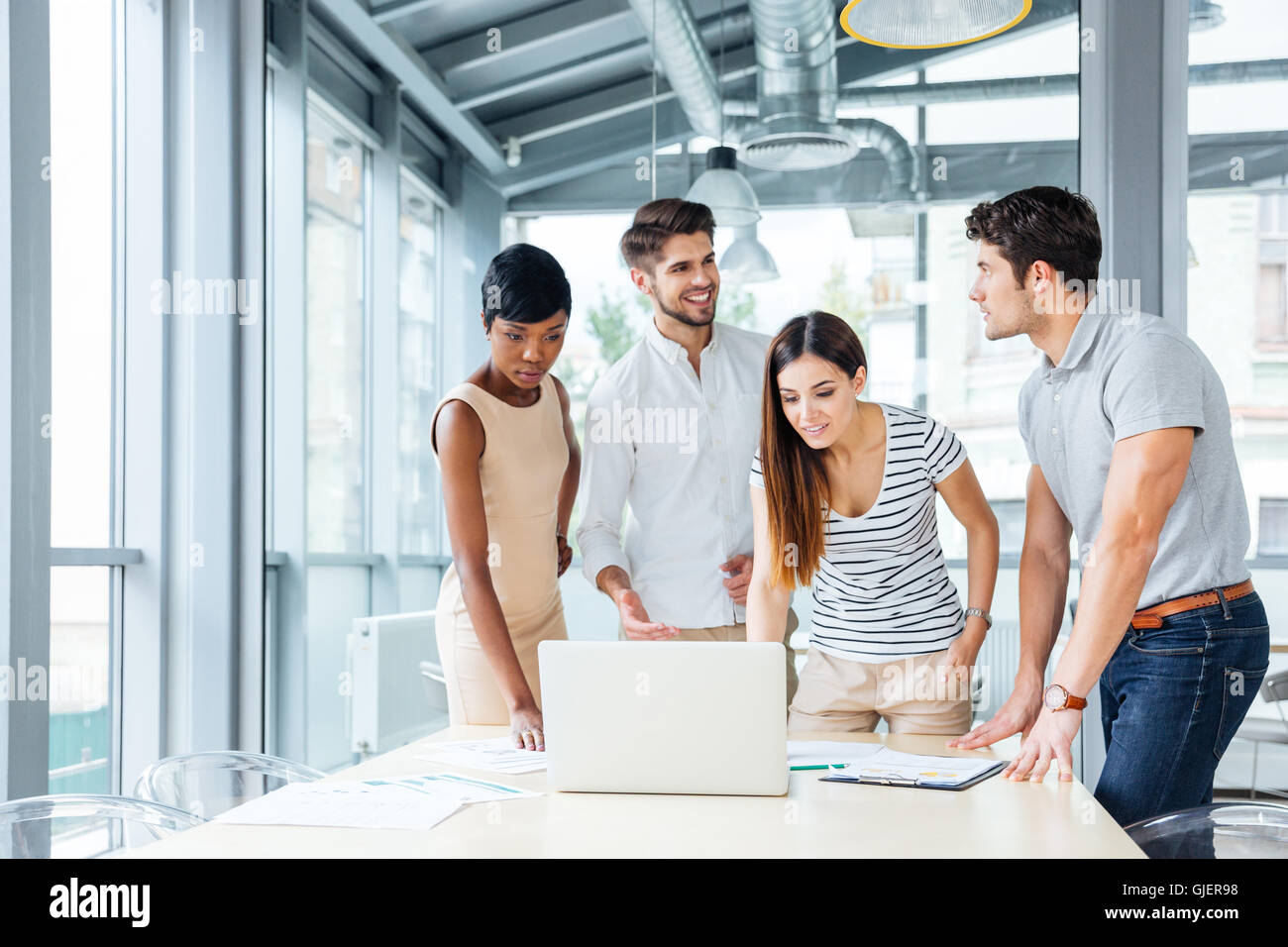 Multiethnic group of happy young business people standing and creating presentation with laptop in office - Stock Image