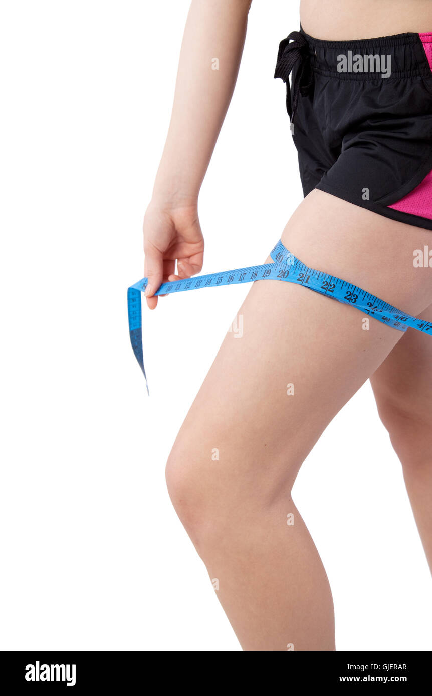 young woman measuring her thigh - Stock Image