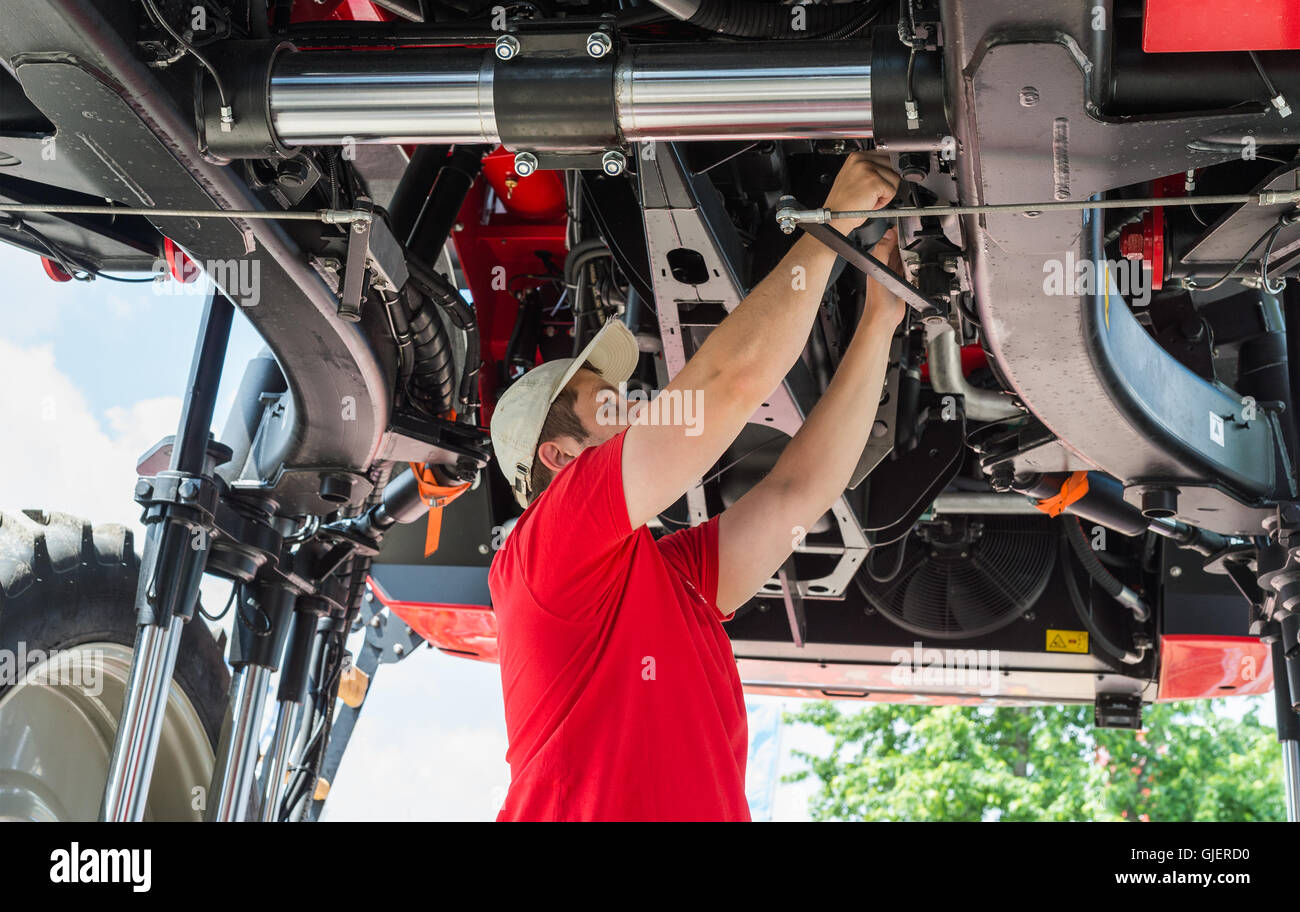 Auto mechanic working underneath a lifted - Stock Image