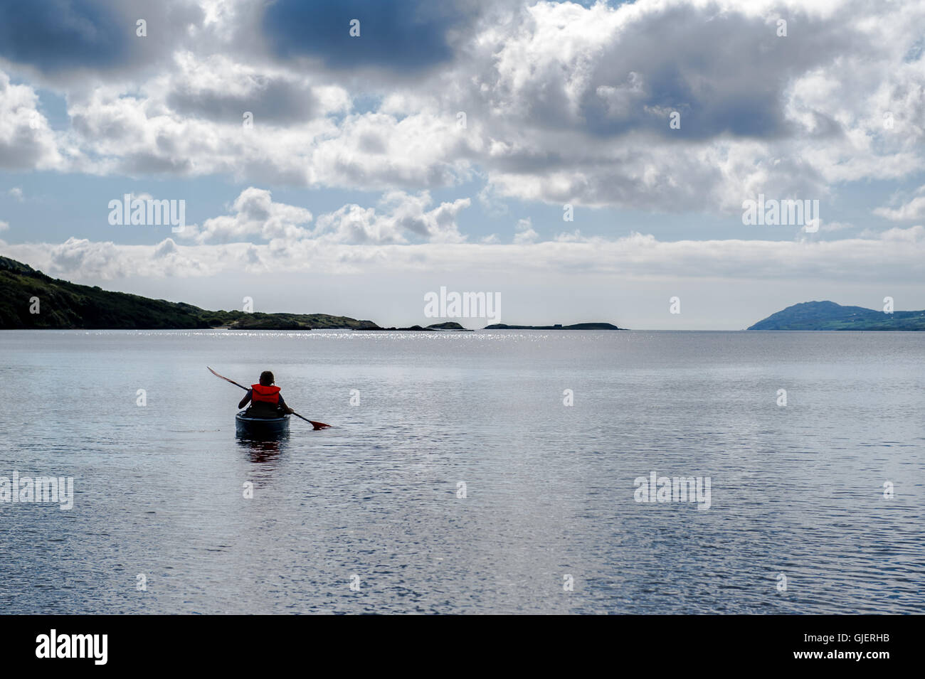A female kayaker paddles away from the sea shore on a calm sea in West Cork, Ireland. - Stock Image