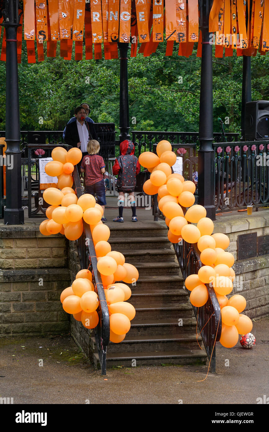 two boys watch singer perform Buxton bandstand covered in orange balloons during art performance  Derbyshire England - Stock Image