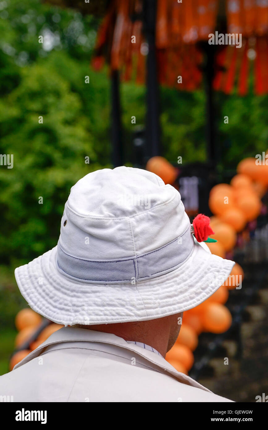 person wearing white hat in front of  bandstand covered in orange balloons during art performance Derbyshire England - Stock Image
