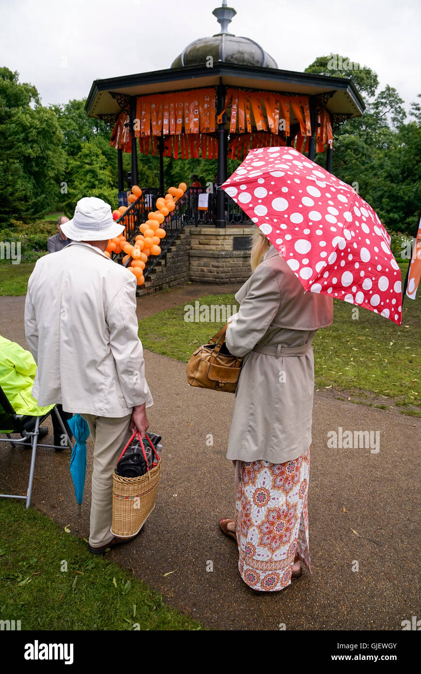 Couple male and female standing in front of bandstand covered in orange balloons during art performance Derbyshire - Stock Image