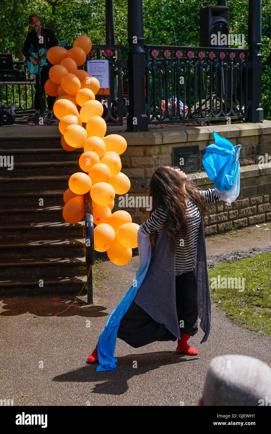Girl dancing in front of Buxton bandstand covered in orange balloons during art performance Derbyshire England - Stock Image