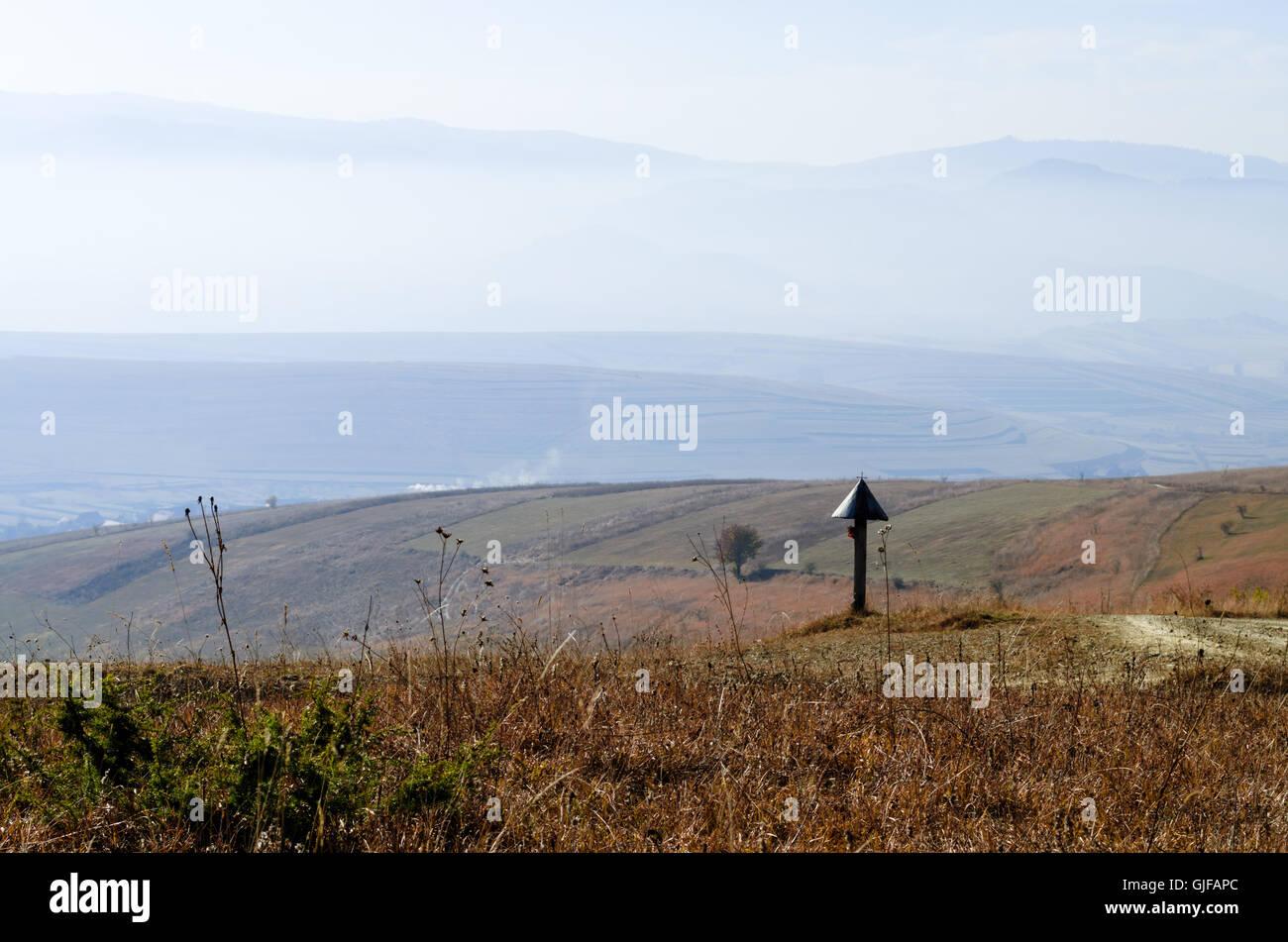 Countryside meadow mountain landscape hills sky, mist, crucifix, scene Stock Photo
