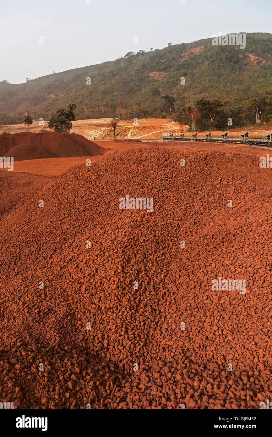 Rail head operations on iron ore mine. Wagons waiting to be loaded from stock piles of lump ore before shipping - Stock Image