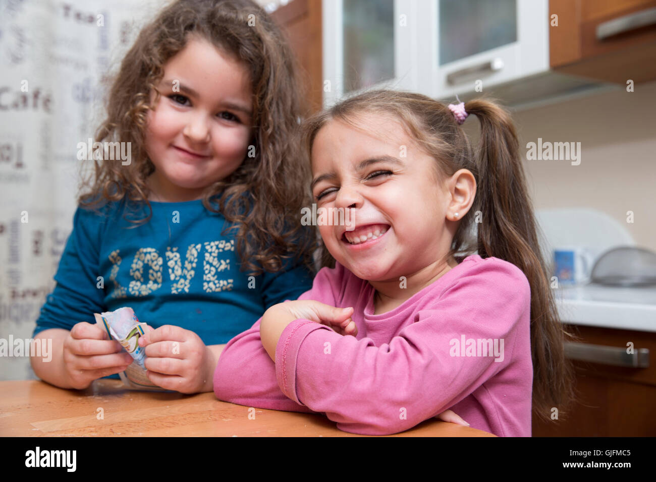 two cute kids smiling and making faces at camera in kitchen stock