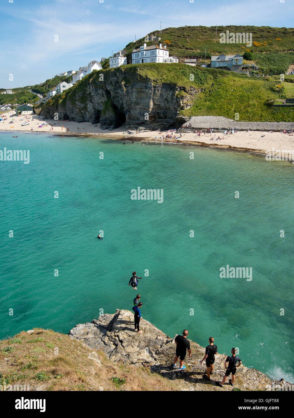 Children jumping in to the sea at high tide in Portreath, Cornwall England UK. - Stock Image