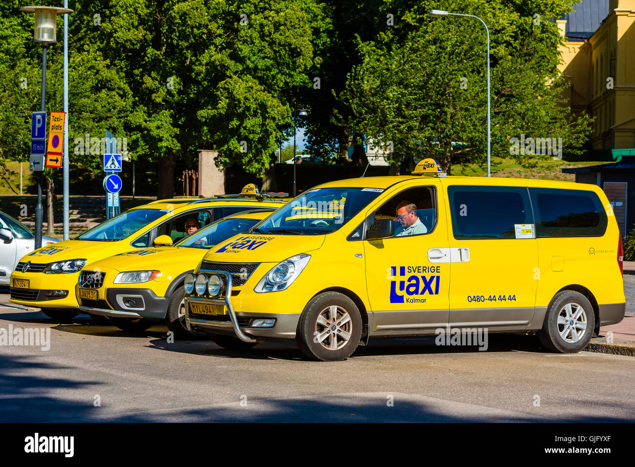 Kalmar, Sweden - August 10, 2016: Three yellow cab or taxi cars waiting for passengers. Sverige Taxi logo on cars. - Stock Image