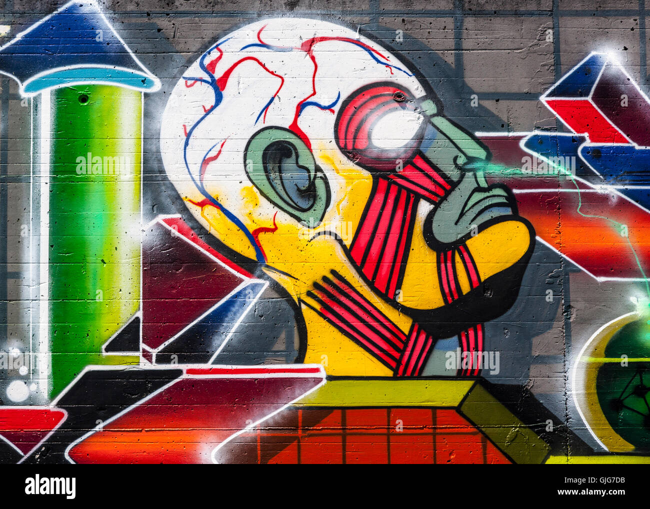 Graffiti head breathing chemical fumes sprayed on the remnant of an old wall, Friedrichshain, Berlin, Germany BHZ. - Stock Image