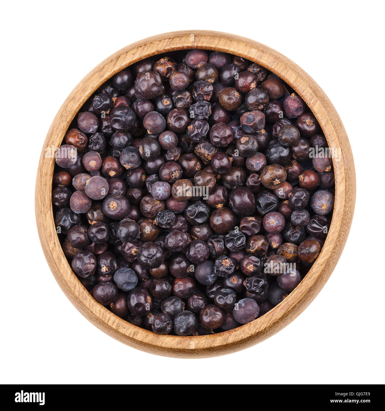 Juniper berries in a bowl on white background. Dried seed cones from Juniperus communis, a conifer, are used as - Stock Image