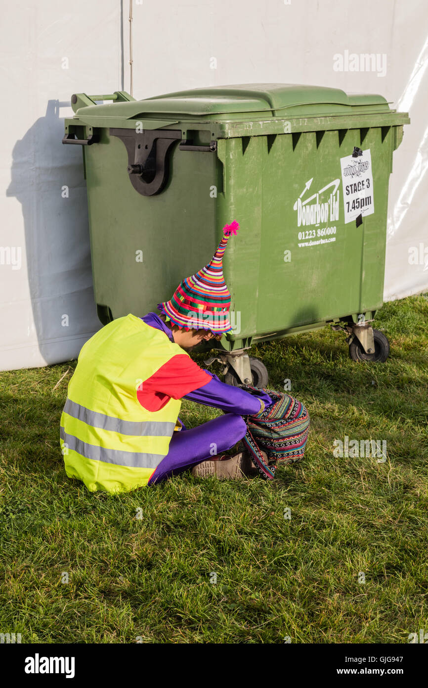 A young man in a colourful pointed hat, searches his bag by a rubbish bin at  Cambridge Rock Festival 2016, Cambridge, - Stock Image
