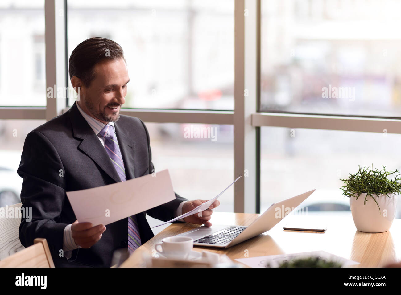 Joyful man working with paper - Stock Image