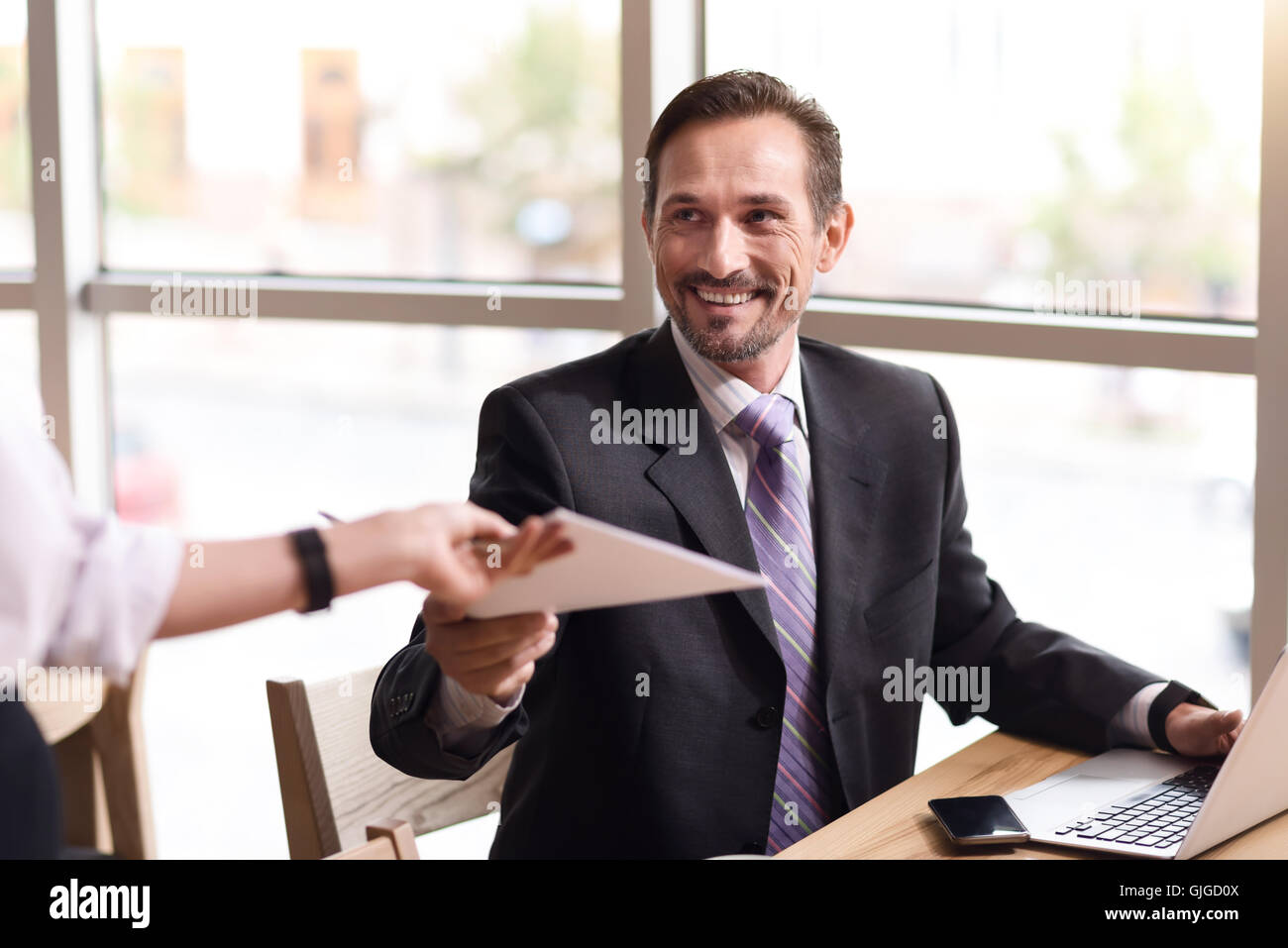 Positive delighted businessman sitting at the table - Stock Image
