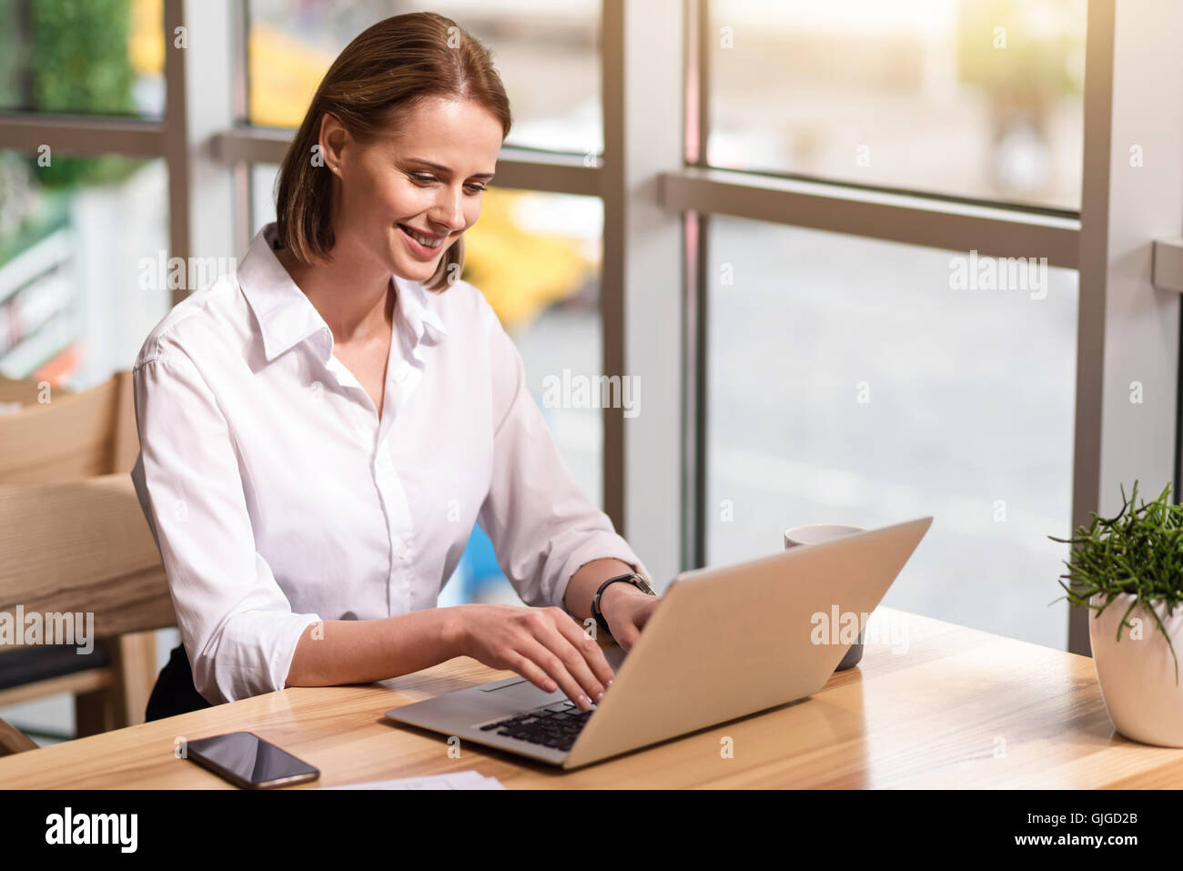 Positive businesswoman sitting at the table - Stock Image