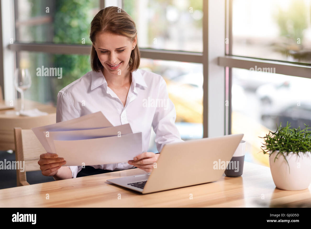 Cheerful woman working with papers - Stock Image