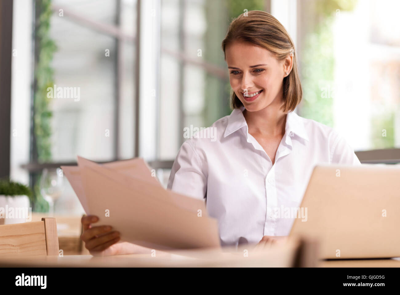 Cheerful business woman sitting in the cafe - Stock Image