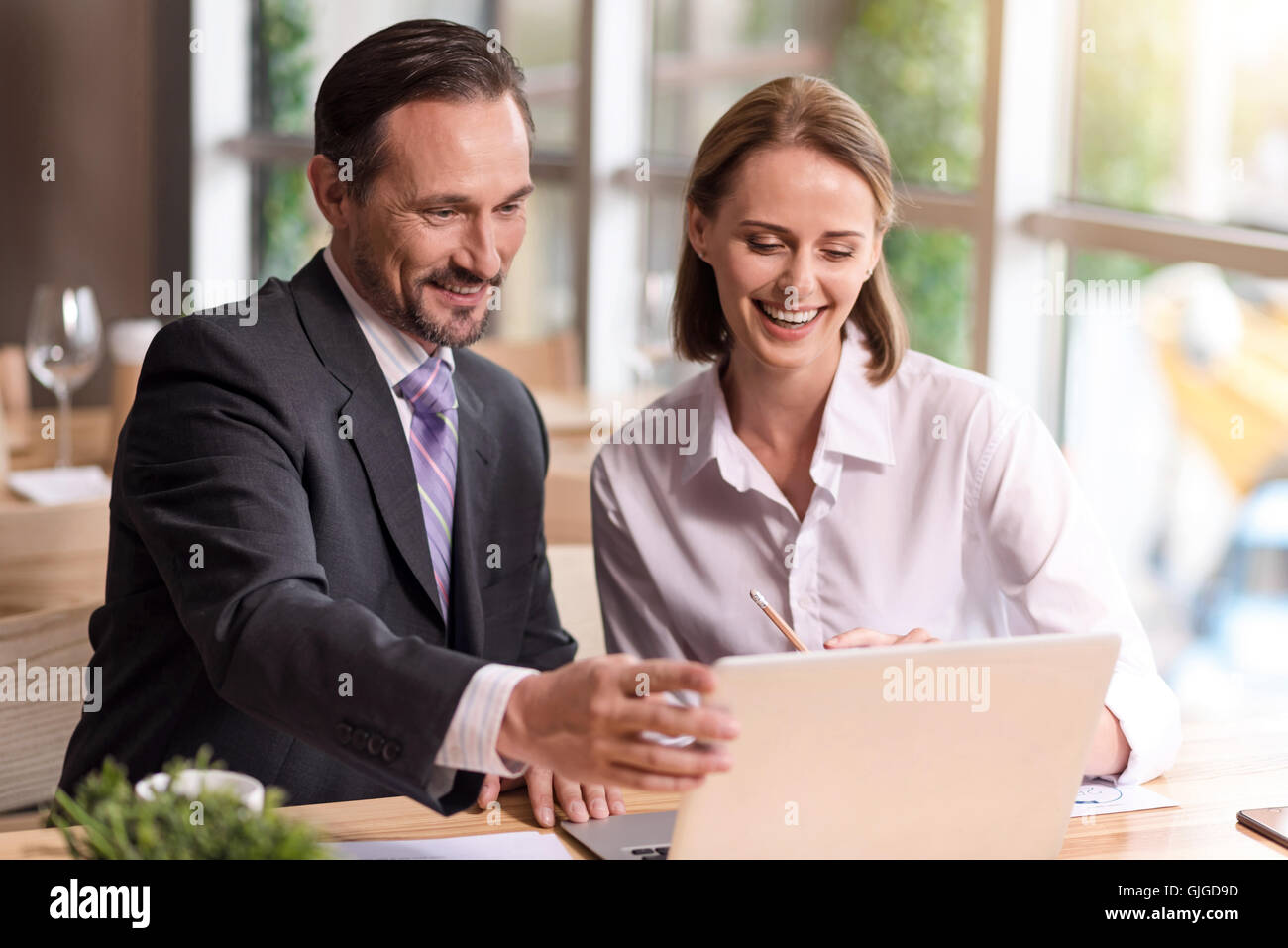 Positive colleagues using laptop - Stock Image