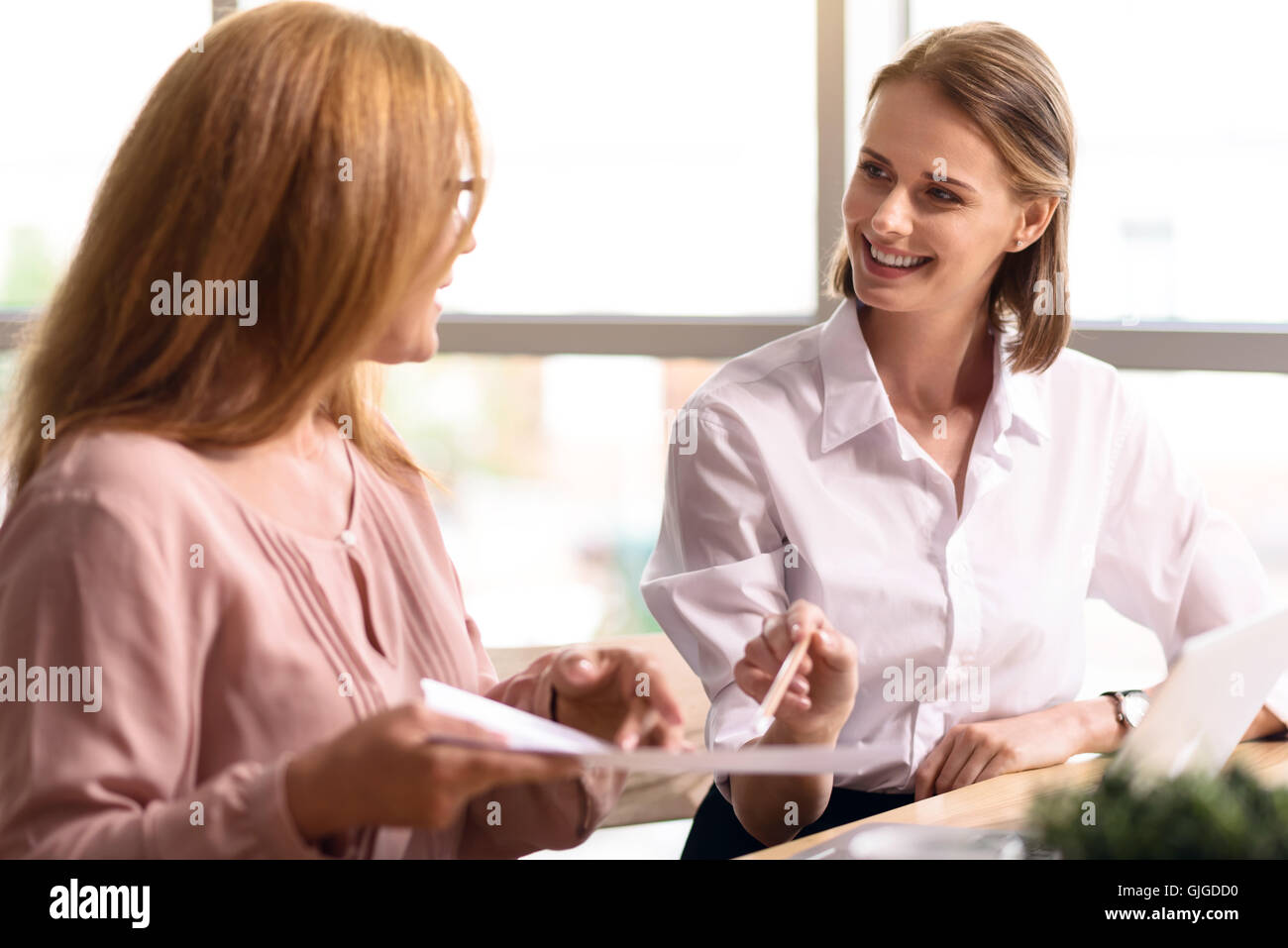 Cheerful smiling colleagues talking - Stock Image