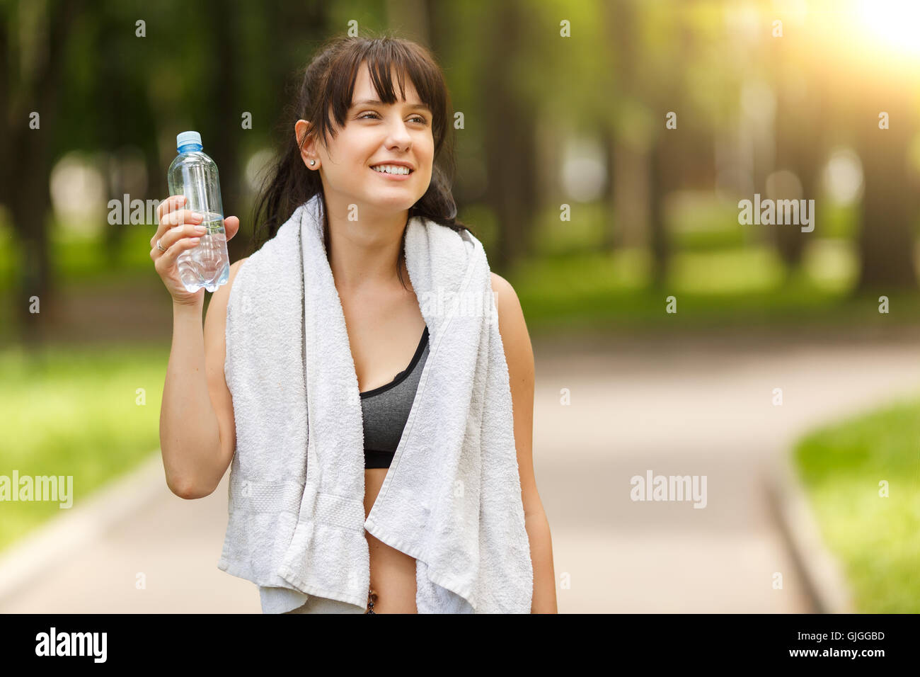 Brunette girl holding bottle of water after sport in park - Stock Image