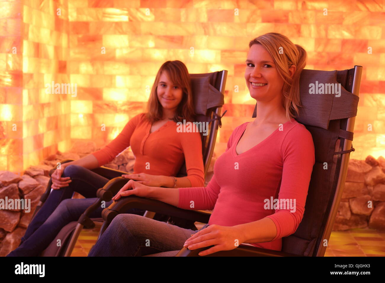 Two happy women relaxing in a holotherapy salt room - Stock Image