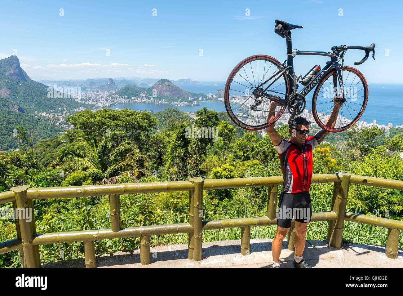 RIO DE JANEIRO - FEBRUARY 24, 2015: Cyclist poses with his bicycle aloft after making the steep ascent to the Vista Stock Photo