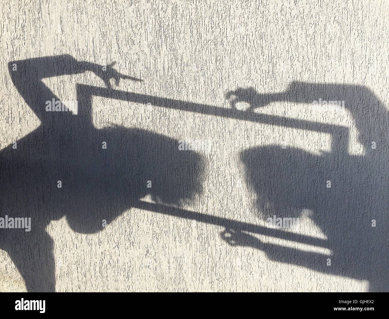 Shadow on wall of two  girls messing about - Stock Image
