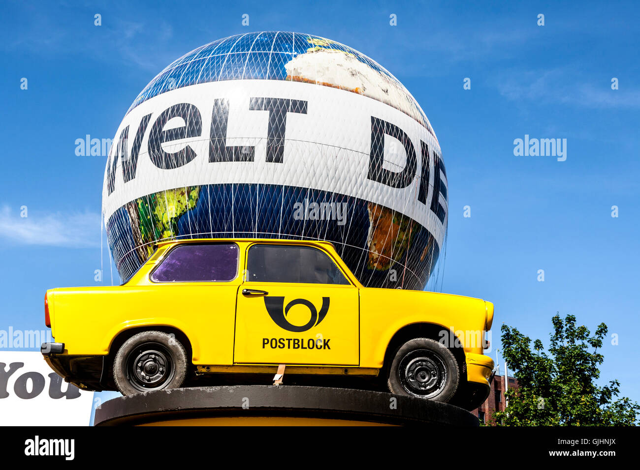 An old yellow Trabant raised up off the ground on a pillar with the Die Welt Balloon behind, Mitte, Berlin, Germany. - Stock Image