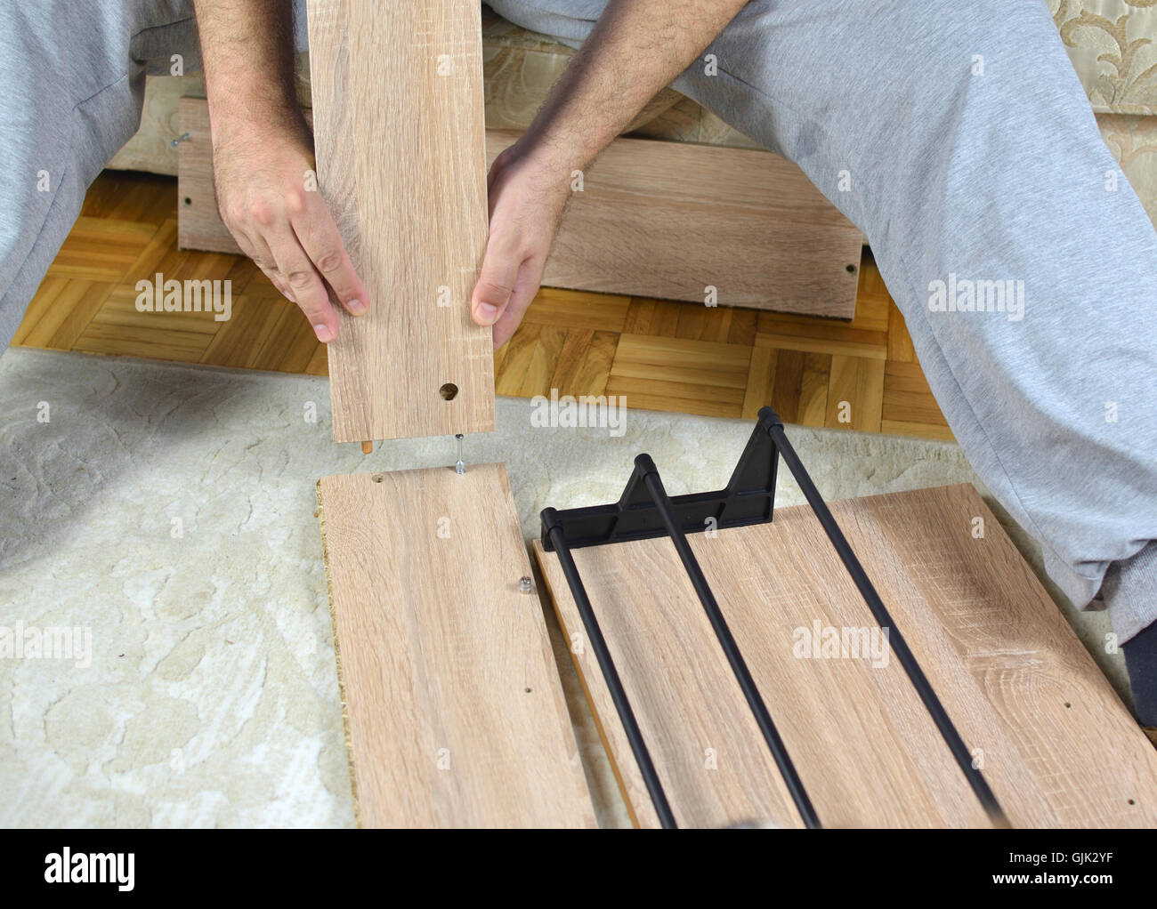 Man Assembling Parts Of A New Shoe Rack Drawer Stock Photo