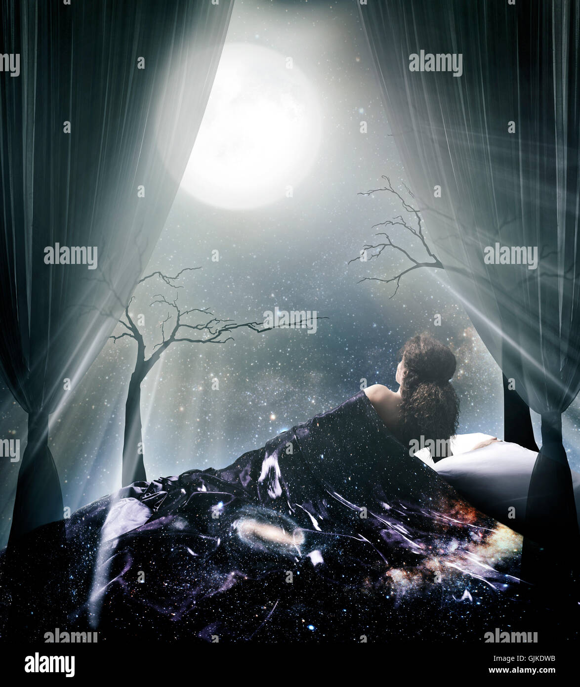 Lit by the moonlight woman lying in bed under the starry sky and the full moon artistic spiritual photo illustration - Stock Image