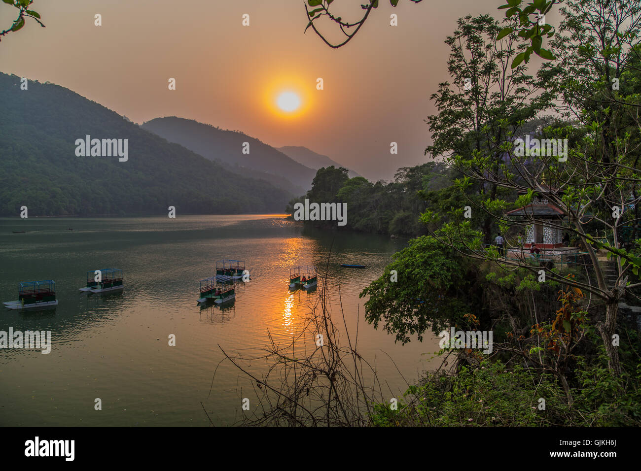 Boats on the lake in Pokhara, Nepal at sunset - Stock Image