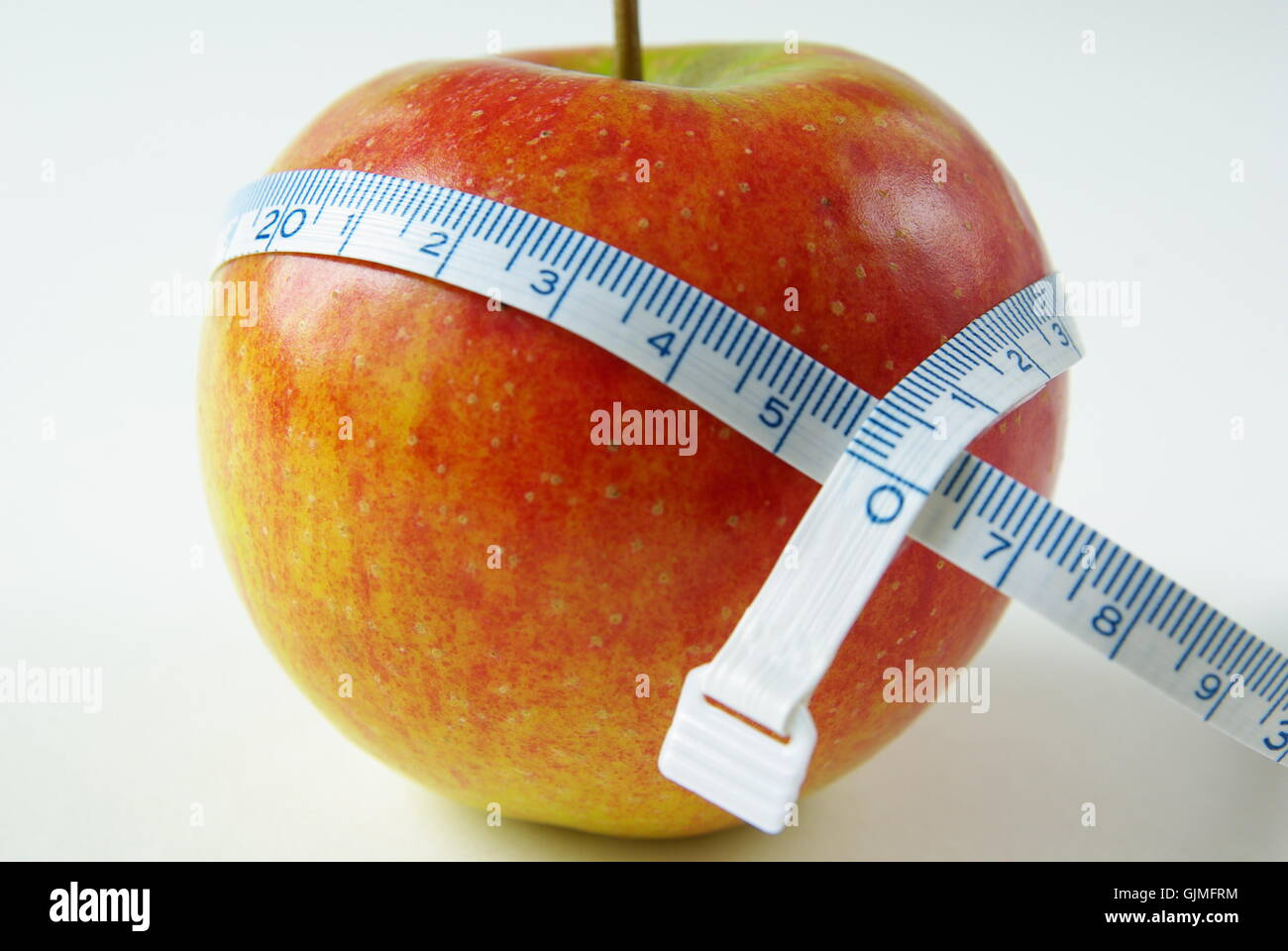 apple with measuring tape as a suggestion for a diet - Stock Image