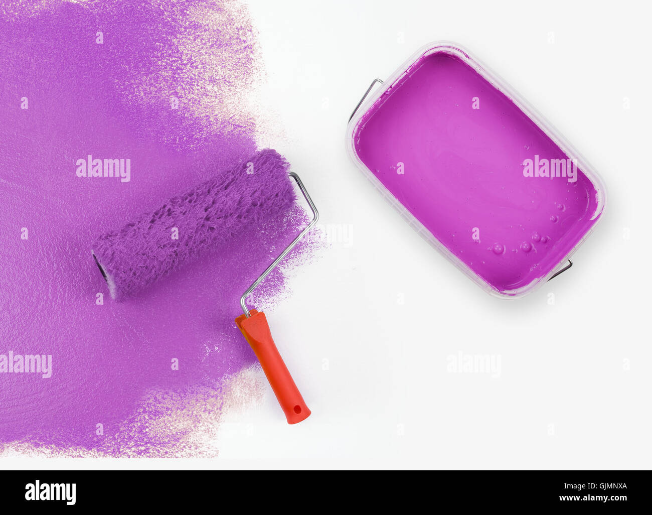 painting magenta roller - Stock Image