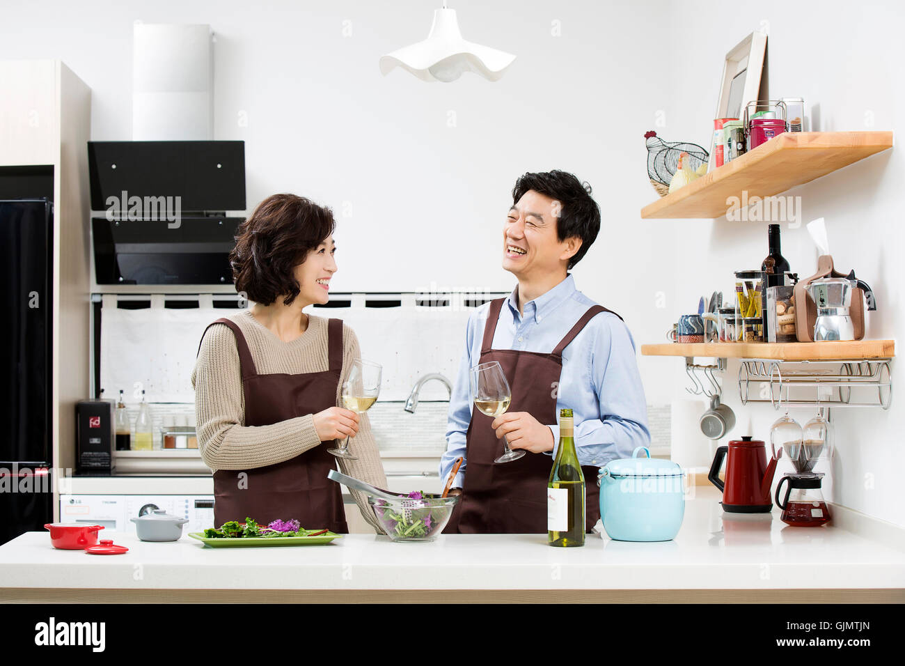 Middleaged Asian Couple Having White Wine in Kitchen Stock Photo ...