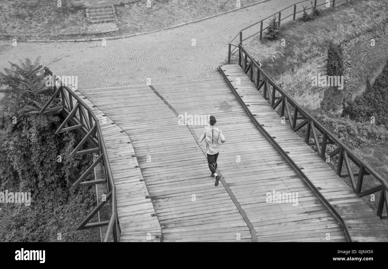 black and white one man run jogging elevated view rear back Stock Photo