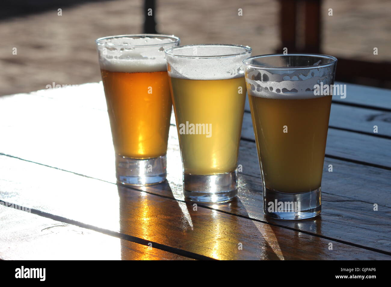 A selection of three craft beers during a tasting session on a wooden table with the sun shining into the glasses - Stock Image