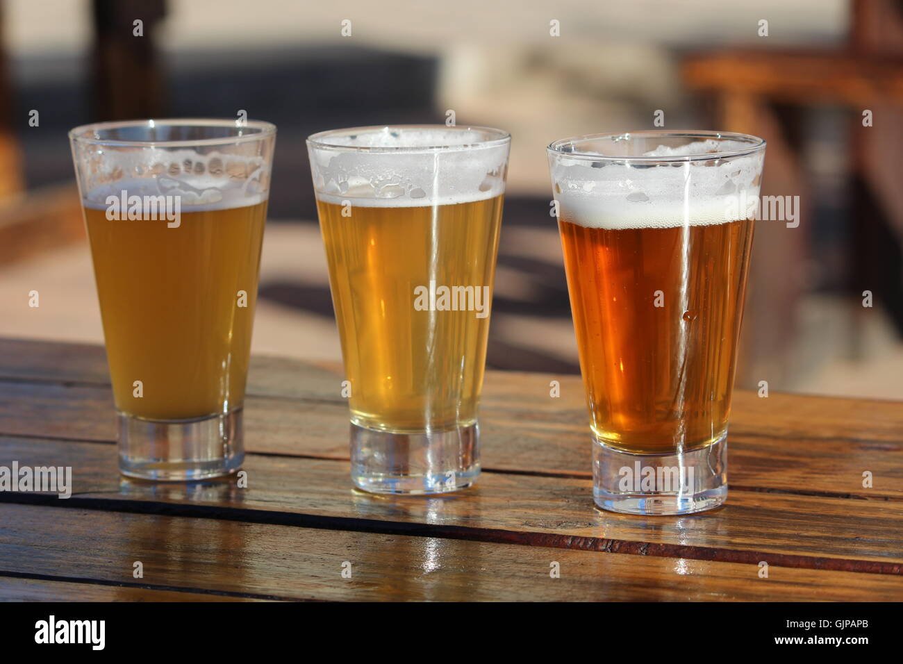 A selection of three craft beers during a tasting session on a wooden table - Stock Image