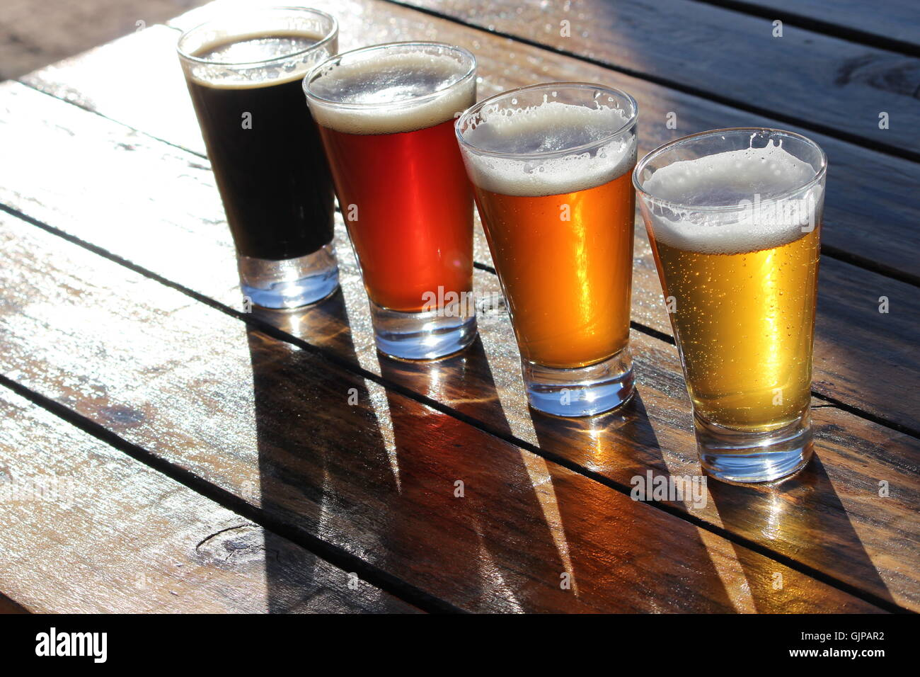 A selection of four craft beers during a tasting session on a wooden table with the sunlight shining through the - Stock Image