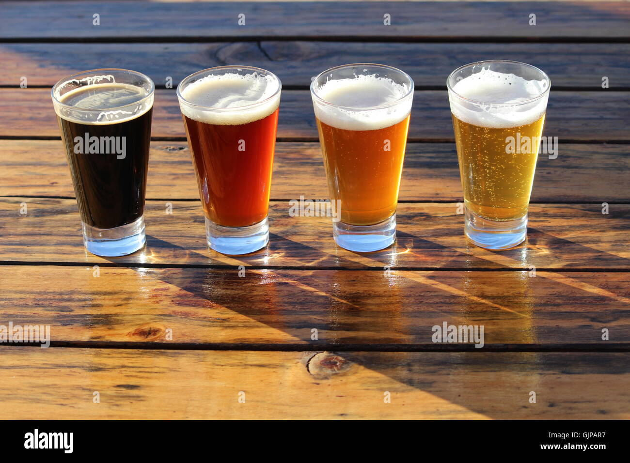 A selection of four craft beers during a tasting session on a wooden table - Stock Image