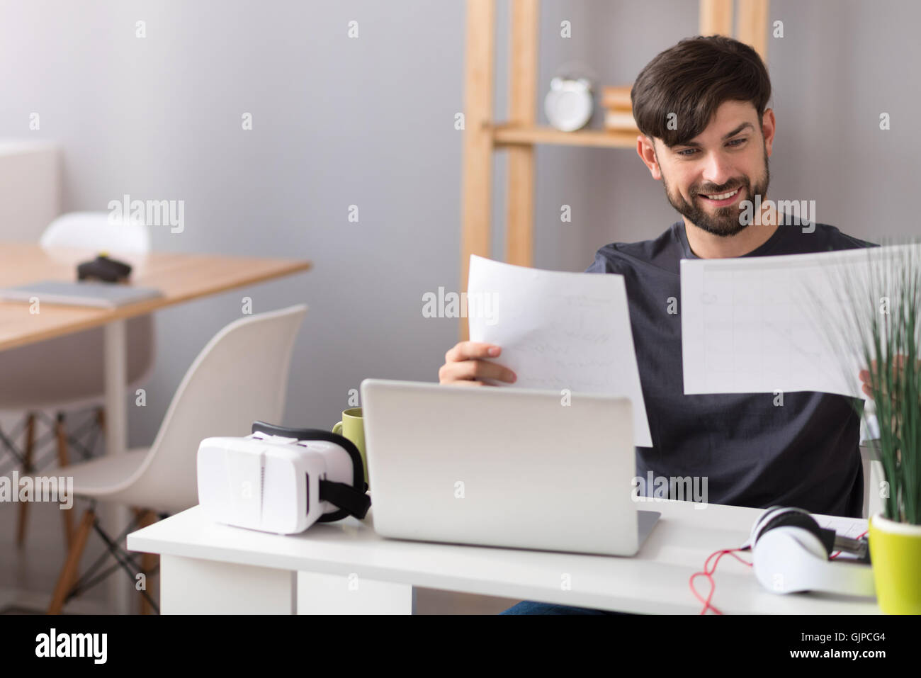 Cheerful man working in the office - Stock Image
