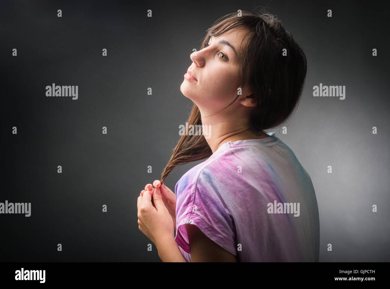 Portrait of melancholic girl isolated on black - Stock Image