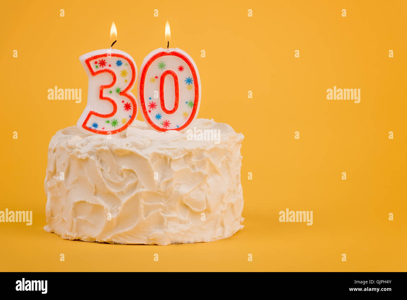 White Frosted Cake With 30 Lit Candles