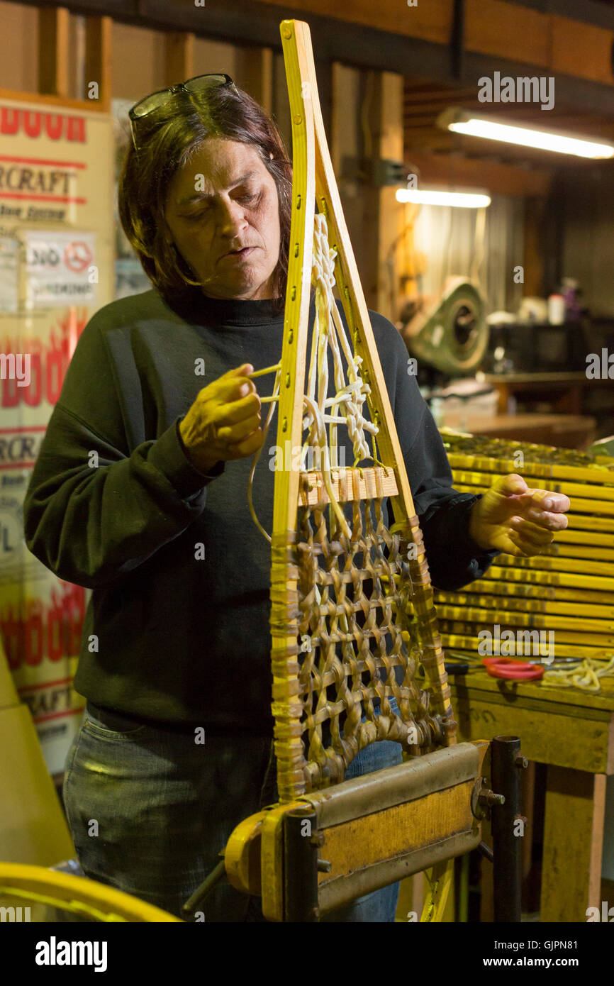 Shingleton, Michigan - Julie Holmes strings snowshoes at the Iverson Snowshoe factory. - Stock Image